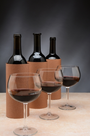 Three different wine bottles and wine glasses set up for a blind wine tasting  The bottles are covered by blank cylinders to hide the label  Vertical format  Wine glasses are partially filled with red wine