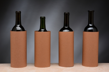 Four different wine bottles set up for a blind wine tasting  The bottles are covered by blank cylinders to hide the label  Horizontal format   photo