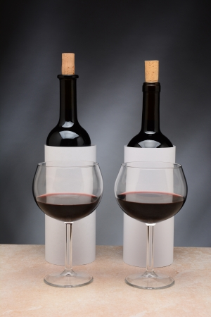 Two different wine bottles and wine glasses set up for a blind wine tasting  The bottles are covered by blank cylinders to hide the label  Vertical format  Wine glasses are partially filled with red wine  photo