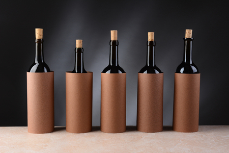Five different wine bottles set up for a blind wine tasting  The bottles have the corks partially removed and are covered by blank cylinders to hide the label  Horizontal format
