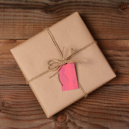 Overhead view of a single holiday package wrapped with eco friendly craft paper and tied with twine. Square format on a rustic wooden table. photo