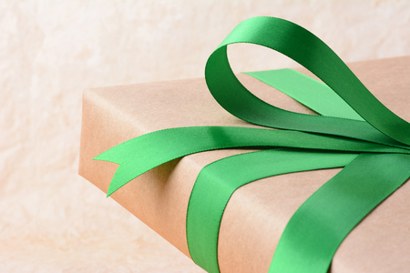 wrapped gift: Closeup of a plain wrapped Christmas gift with green ribbon and bow. Shallow depth of field only showing part of the present. Horizontal format. Stock Photo