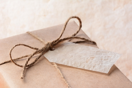 Closeup of a brown eco friendly paper wrapped package with gift tag. Horizontal format with shallow depth of field.