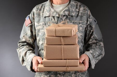 fatigues: Closeup of a soldier wearing camouflage fatigues holding a stack of packages for mail call  Horizontal format, man is unrecognizable