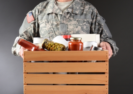 charity collection: Closeup of a soldier in fatigues holding a wooden box full of canned and packaged food for a holiday charity drive  Horizontal format man is unrecognizable