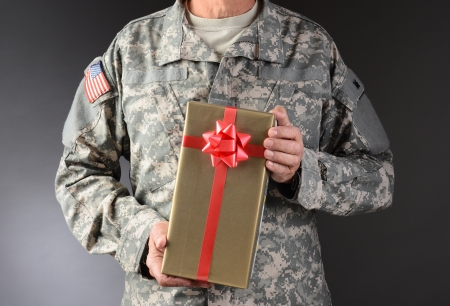 Closeup of a soldier holding a Christmas present  The gift is wrapped in gold paper with red ribbon and bow  Horizontal format  Man is unrecognizable