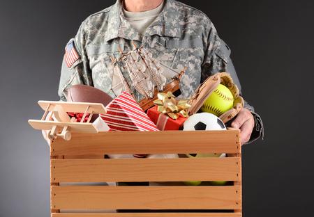 futbol infantil: Primer plano de un soldado en uniforme de la celebraci�n de una caja de madera llena de juguetes y equipos deportivos en un formato horizontal hombre campa�a de caridad de vacaciones es irreconocible Foto de archivo