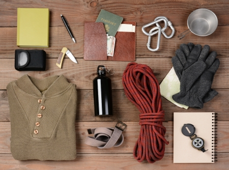 backpackers: Overhead view of gear laid out for a backpacking trip on a rustic wood floor. Items include, rope, gloves, sweater, carabiners  book, belt, cup, passport, wallet, canteen, compass, money, map, knife