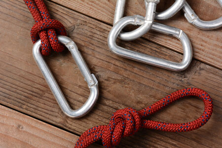 Closeup of a climbing rope and carabiners on a rustic wooden cabin floor. Horizontal format.