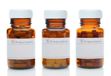 Closeup of three brown medicine bottles filled with different pills and medications with their caps on over a white background with reflection. The glass bottles have blank labels. Horizontal format.