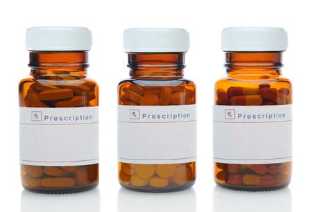 recetas medicas: Primer plano de tres botellas de medicina marrones llenos de diferentes pastillas y medicamentos con sus tapas en más de un fondo blanco con la reflexión. Las botellas de vidrio tienen etiquetas en blanco. Formato horizontal. Foto de archivo