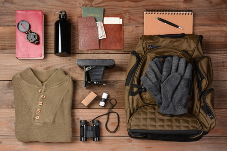 Overhead view of gear laid out for a backpacking trip on a rustic wood floor. Items include, Backpack, gloves, sweater, camera, film, binoculars, passport, wallet, canteen, compass, money,  photo