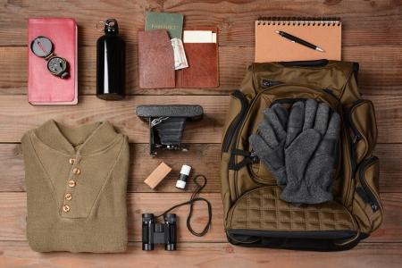 mochila viaje: Vista de arriba del engranaje dispuesto para un viaje de mochilero en un piso de madera r�stica. Los art�culos incluyen, Mochila, guantes, su�ter, c�mara fotogr�fica, filmadora, binoculares, pasaporte, billetera, cantina, la br�jula, el dinero,