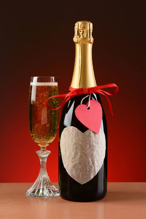 Closeup of a champagne bottle decorated for Valentines Day  A glass of champagne is next to the bottle  The bottle has a red ribbon and heart shaped tag and a blank heart shaped label