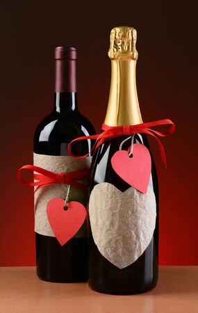 Champagne and wine bottles decorated for Valentines Day  The bottles have red ribbons and heart shaped tags  Vertical format on a light to dark red background  photo