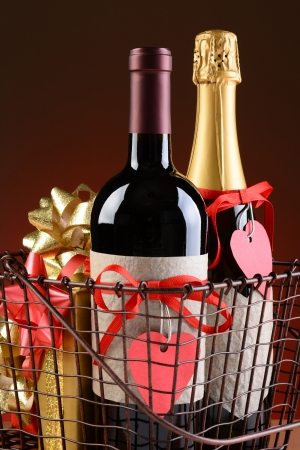 Closeup of a wire shopping basket with Valentines Presents  Vertical Format on a light to dark red background  Items include champagne, wine, gift boxes  The bottles have red ribbons and heart shaped gift tags