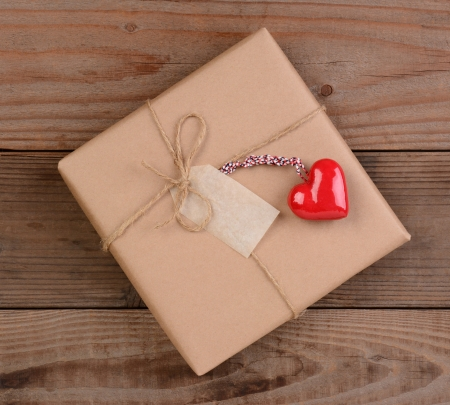 High angle view of a plain brown paper wrapped Valentines Day present with a ceramic red heart. Square format on a rustic wood surface. photo