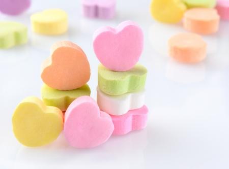 cuore: Primo piano di caramelle cuori di San Valentino su una superficie riflettente bianco in formato orizzontale con fuori di caramelle fuoco in background
