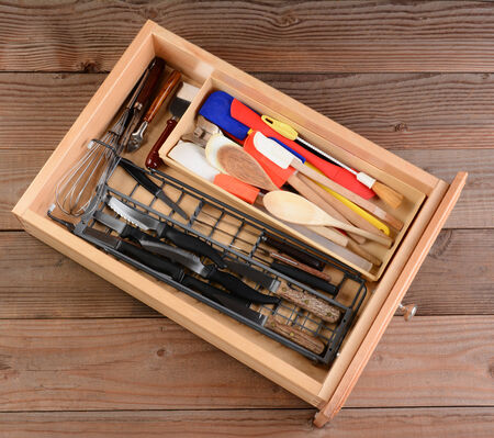 High angle view of a kitchen drawer on a rustic wooden table. The drawer is full of wooden spoons, knives, whisks, spatulas, and other household kitchen items.