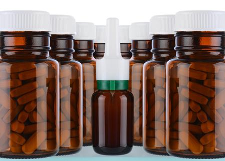 A variety of brown glass medicine bottles on a shelf over a white background. photo