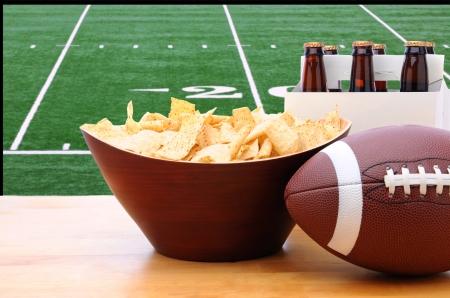 pelotas de futbol: Chips, f�tbol y Six-pack de cerveza en una mesa delante de una gran pantalla de televisi�n con un campo de f�tbol Foto de archivo