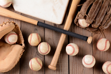 baseball equipment on a rustic wood surface. Items include, baseballs, bats, home plate, catchers mitt and glove.