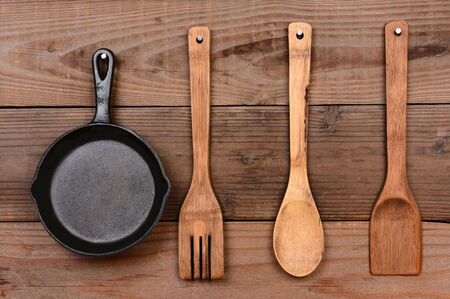 cast iron: Closeup of a cast iron frying pan and wooden utensils hanging on the wall of a rustic kitchen.