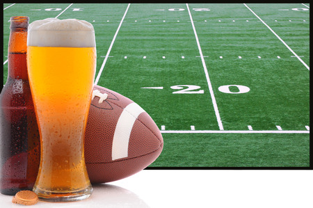 A frothy glass of beer with an American Football in front of a big screen television  Great for Super Bowl themed projects