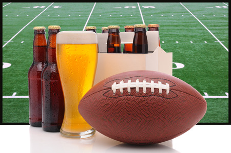 6 pack beer: Six pack of beer and frothy glass with an American Football in front of a big screen television  Great for Super Bowl themed projects  Stock Photo