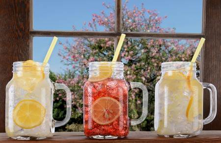 thru: Glasses of lemonade and fruit juice on a window ledge on a bright sunny summer day  The mason jar style glasses have handles and drinking straws  Thru the window is a tree and blue sky