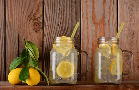 Glasses of lemonade and lemons on a ledge in front of a rustic wooden kitchen wall