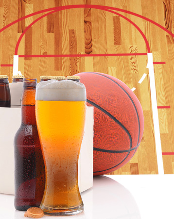A Basketball Six Pack of Beer Bottles and a Glass of Ale on a white table top with Court in background