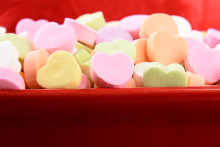 candy hearts: Closeup of assorted pastel candy hearts for Valentines Day in a red ceramic candy bowl