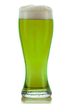 A cold frothy glass of green beer photo