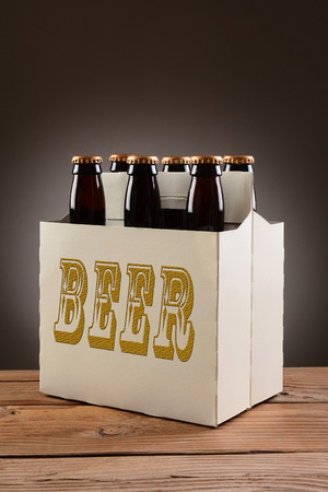6 pack beer: Closeup of a six pack of brown beer bottles with the word BEER written on the side, sitting on a rustic wooden table Stock Photo