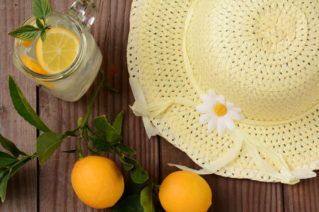 Fresh Squeezed Lemonade on a rustic wooden table with lemons and a yellow sun hat. Horizontal format with an oldtime feel, shot from a high angle. photo