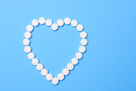 Aspirin in the shape of a heart. The white tablets are arranged in heart shape on a blue background. The heart is off set to one side leaving copy space.