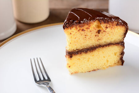 A slice of yellow cake with chocolate frosting on a white plate with a fork.