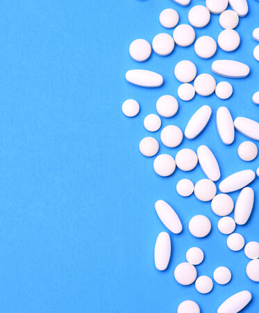ot: A group of white pills and tablets randomly arranged on a blue background. The pills are off set ot one side leaving lots of copy space. Stock Photo