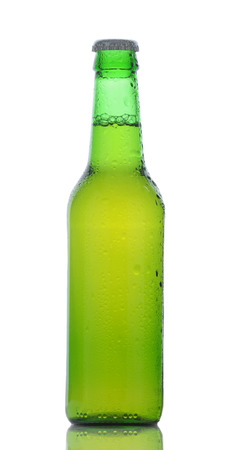Closeup of a green beer bottled covered in condensation on a white background with reflection. Stock Photo