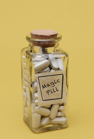 Closeup of an old fashioned pill bottle filled with Magic Pills Stockfoto