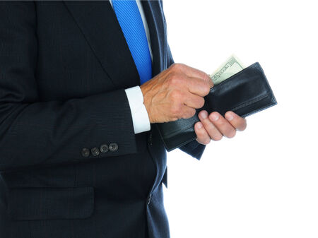 payola: Closeup of a businessman wearing a dark suit taking money from his wallet.  Horizontal format over a white background only showing the mans torso and hands.