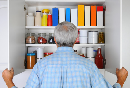 Gros plan d'un homme d'âge mûr regarder dans son garde-manger Banque d'images - 26586810