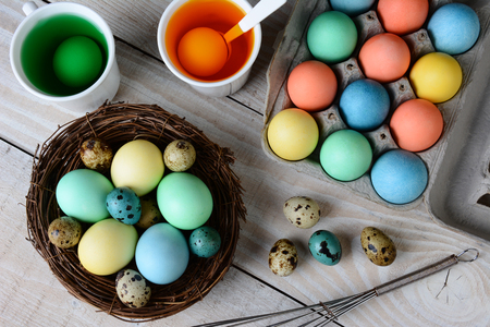 hard boiled: High angle view of Easter Egg dying. Dyed eggs in a nest with eggs in dye solution and other eggs ready to be dunked. Horizontal format on a rustic farmhouse style kitchen table. Stock Photo