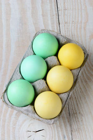 high angle shot: High angle shot of a six pack of Easter eggs on a rustic farmhouse kitchen table. Vertical format.