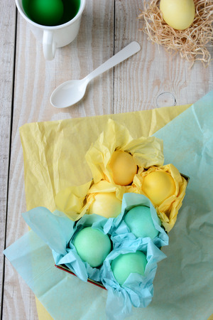 High angle view of a box of pastel Easter eggs wrapped with tissue paper. The box is on a rustic farmhouse style kitchen table with a cup spoon and dyed egg in a nest in the background. photo