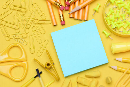 School supplies. Pencils, erasers, paper clips, brushes, pins, scissors, paper laying in a random pattern on a yellow background. Everything in a shade of yellow except for the blue note pad. photo