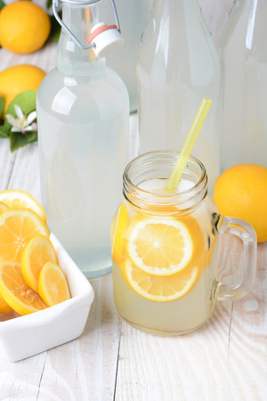 Old fashioned sparkling lemonade shot from a high angle. Vertical format on a rustic wooden farmhouse style table. photo