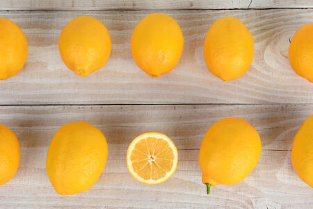 high angle shot: High angle shot of two rows of whole lemons filling the frame with one cut piece of fruit. Horizontal format or a rustic farmhouse style table.