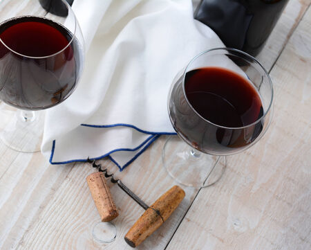 cork screw: Two wineglasses of red wine on a wood table with antique cork screw. Horizontal format shot from a high angle.